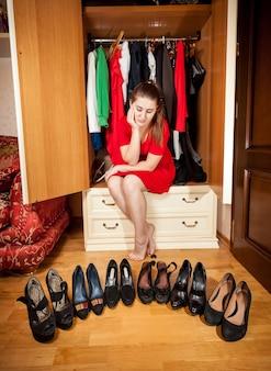 Bella donna triste che sceglie scarpe col tacco alto nere al guardaroba