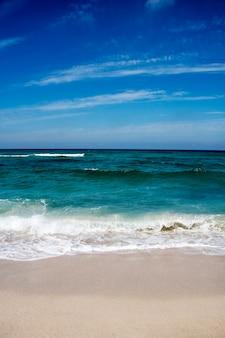 Bella spiaggia sabbiosa e morbida onda blu dell'oceano