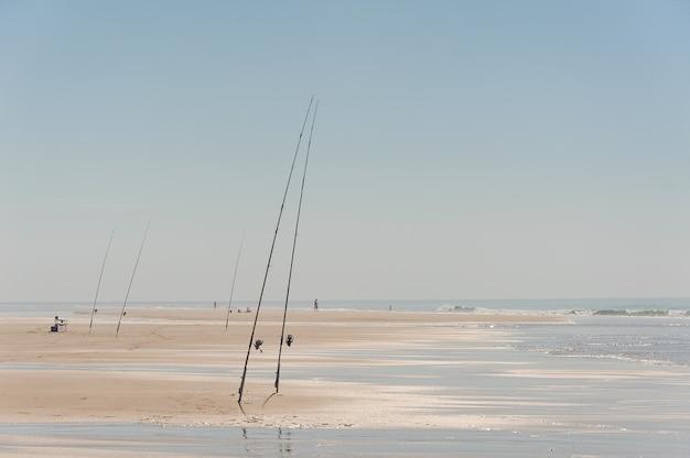 Bellissimo mare sabbioso con canne da pesca e fishman che ha un periodo di riposo vicino all'acqua sotto il cielo blu