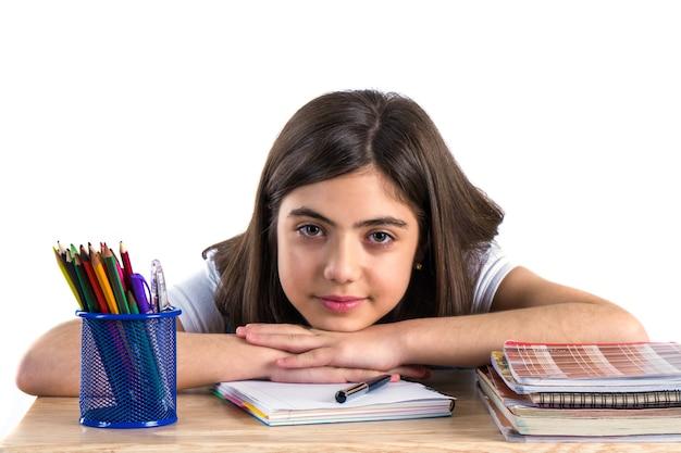 Una bella scolaretta si siede alla scrivania e pensa white