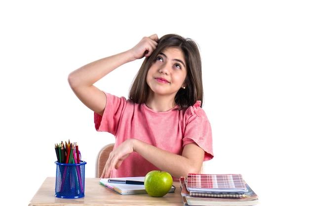 Una bella scolaretta si siede alla scrivania con la mela e il pensiero bianco