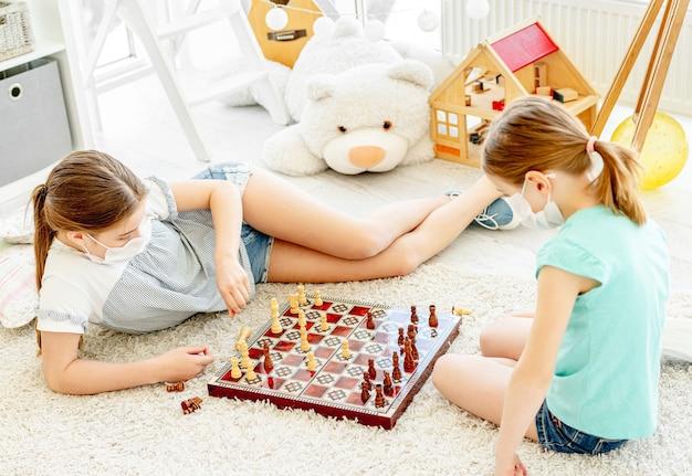 Belle ragazze della scuola in maschere mediche che giocano a scacchi durante la quarantena a casa