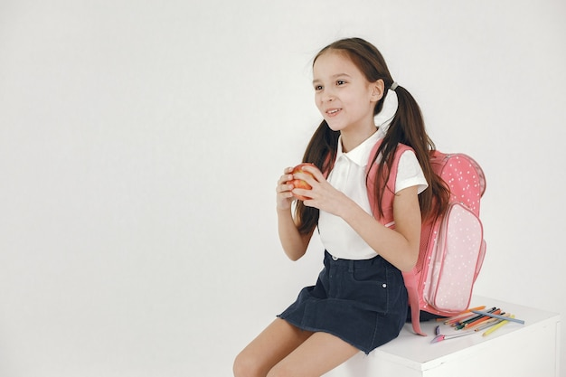 Bella scolara che mangia mela isolata