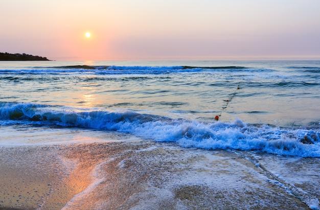 Bella vista di alba della spiaggia del mare con la riflessione del sole sull'acqua.