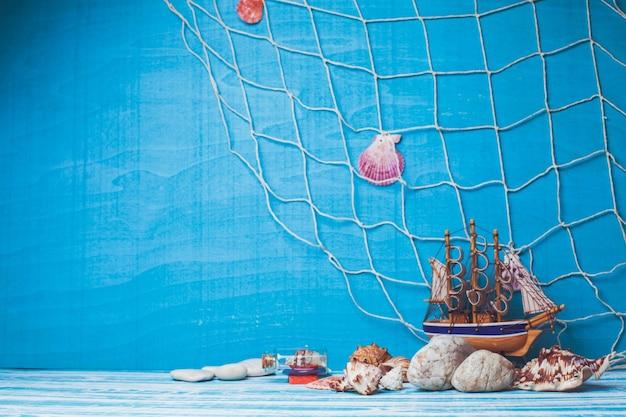 Bella composizione marina con barca a vela giocattolo, conchiglia, bottiglia di vetro e rete da pesca su sfondo blu