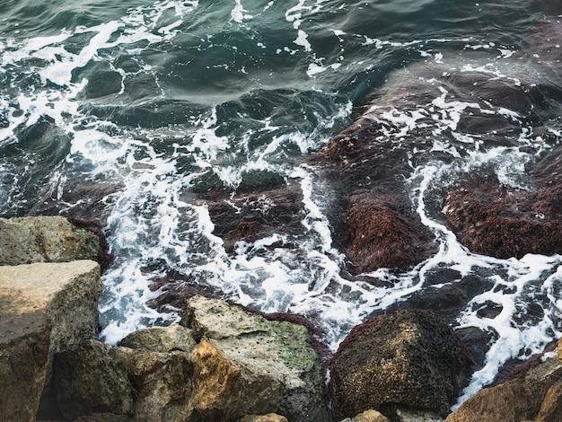 Bella spuma marina, onde tempestose e rocce