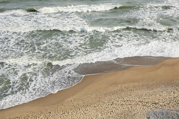 Bellissimo mare con onde sulla spiaggia sabbiosa