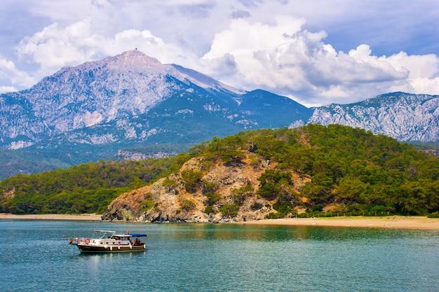 Bella vista sul mare. giornata estiva in una baia con montagne e cielo fantastico e una barca. tacchino. antalya.