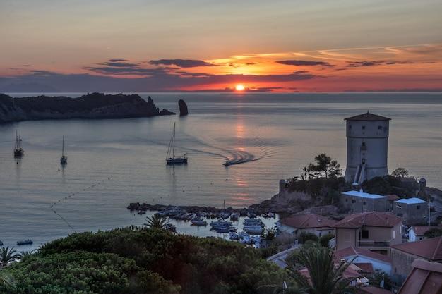 Bella vista sul mare al tramonto con un faro e barche