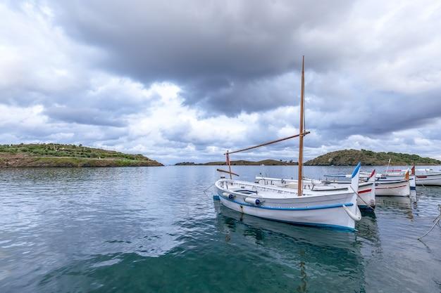 Bella vista sul mare con barche da pesca sotto il cielo drammatico.