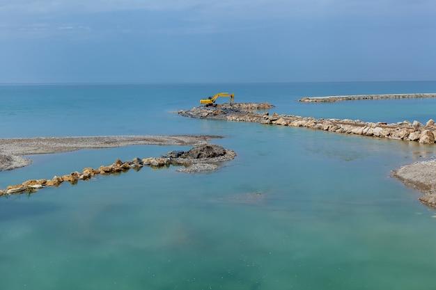 Un bellissimo paesaggio marino con moli in pietra sullo sfondo di un cielo azzurro puro.