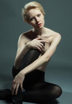 Bella e seducente donna seduta in posa alla moda con indosso collant neri