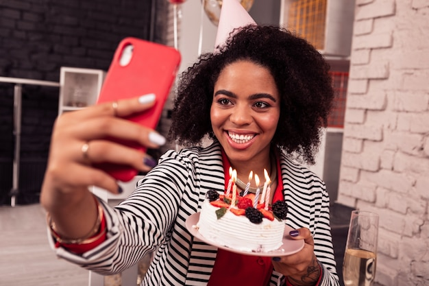 Bellissimi selfie. bella donna positiva che scatta foto mentre mostra la sua torta di compleanno