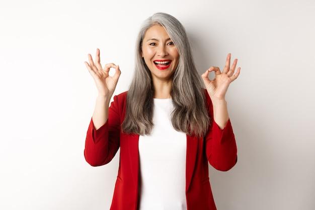 Bella donna asiatica senior in giacca sportiva rossa, sorridente e mostrando segni ok, approva e dice sì, in piedi su sfondo bianco.