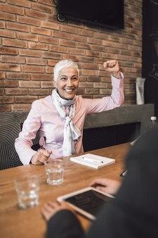 Bella donna d'affari senior felice dopo aver condotto un colloquio di lavoro.