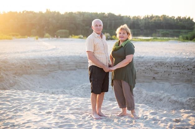 Belle coppie senior nell'amore fuori in spiaggia in natura di estate