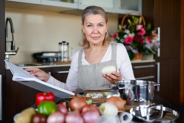 Bella donna senior in grembiule sta leggendo un libro di ricette, mentre cucina in cucina