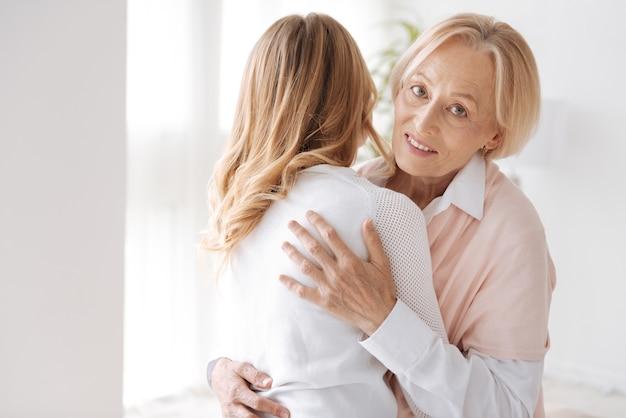 Bella donna senior che abbraccia la sua figlia dai capelli dorati in piedi con la schiena in avanti