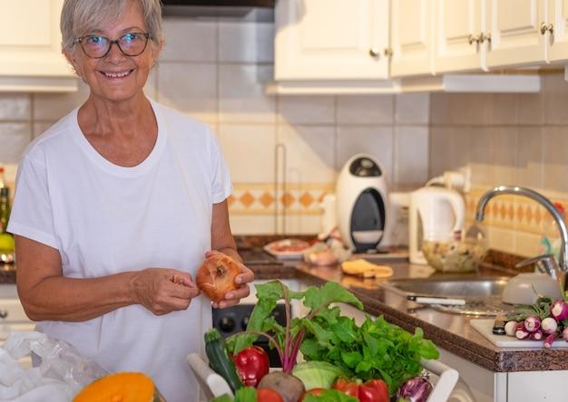 Bella donna anziana nella cucina di casa che prepara le verdure. crudo fresco raccolto in tavola