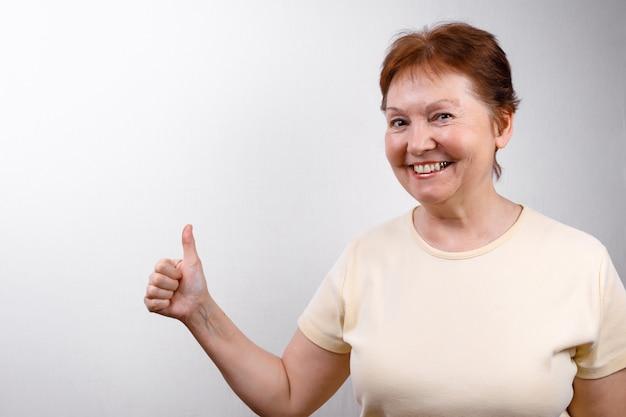 La bella donna senior guarda sorpresa alla struttura su bianco in una maglietta leggera