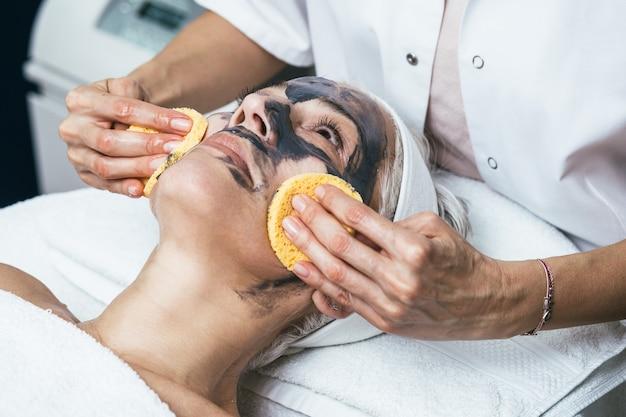 Bella donna anziana che riceve maschera facciale di argilla con effetti ringiovanenti nel salone di bellezza della stazione termale.