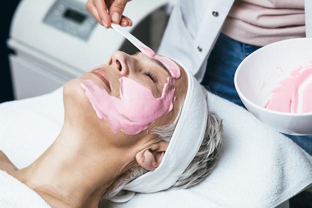 Bella donna anziana che riceve maschera facciale con effetti ringiovanenti nel salone di bellezza spa.
