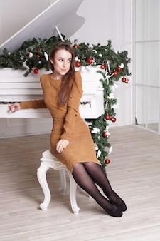 Bella ragazza bruna sensuale con lunghi capelli lisci vicino a un pianoforte bianco con decorazioni natalizie