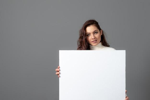 La bella donna sensuale di affari con capelli ricci lunghi mostra un tabellone per le affissioni in bianco, isolato su gray, spazio della copia