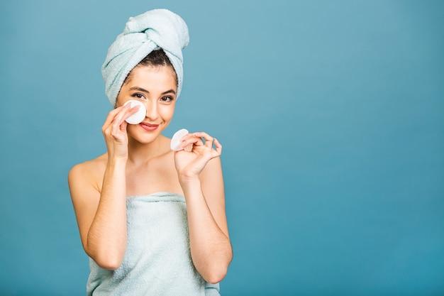 Bella ragazza sensuale che pulisce il viso con un tampone di cotone. foto della ragazza dopo il bagno in accappatoio e asciugamano sulla sua testa isolato su sfondo blu.