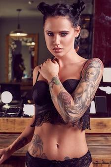 Bella ragazza sensuale con tatuaggio indossando lingerie nel negozio di barbiere