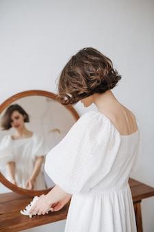 Bella donna timida sensuale in un vestito bianco che sta davanti ad uno specchio rotondo. bruna con i capelli corti al chiuso. da dietro.