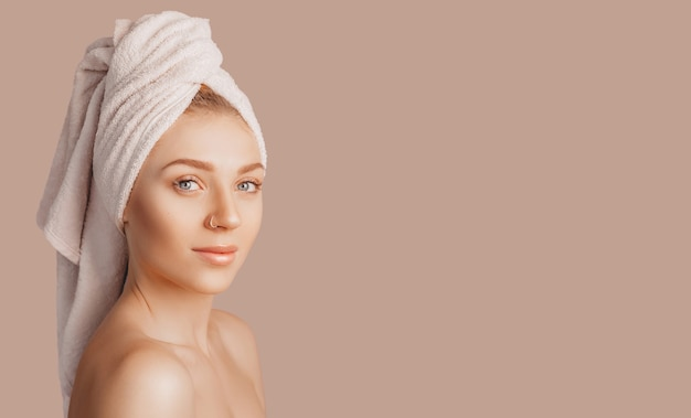 Bella ragazza sensuale con pelle pulita su un fondo beige con un modello. donna in topless in un asciugamano. il concetto di trattamenti termali, bellezza e cura naturali, giovinezza, crema e maschera, freschezza
