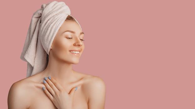 Bella ragazza sensuale con pelle pulita su uno sfondo rosa con un modello. donna in topless in un asciugamano. il concetto di trattamenti termali, bellezza e cura naturali, giovinezza, crema e maschera, freschezza