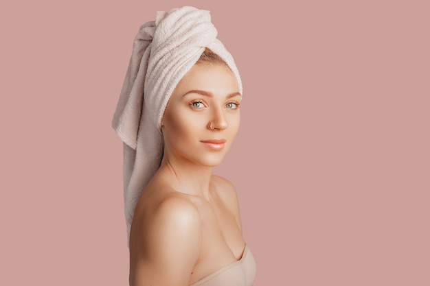 Bella ragazza sensuale con la pelle pulita su una parete rosa