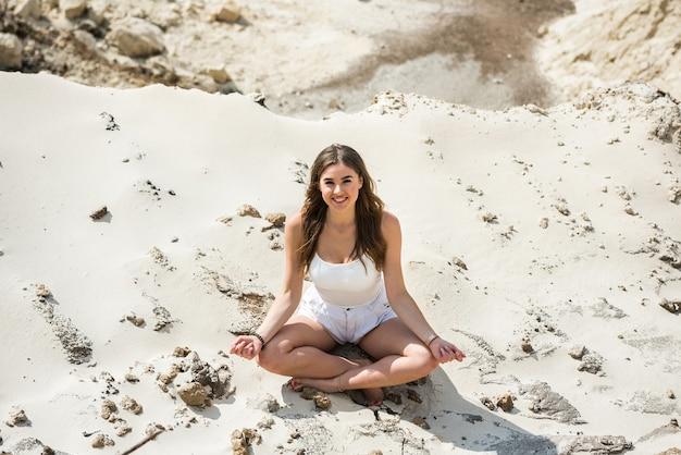 La bella giovane donna sensuale in vestiti bianchi chiari si trova sulla terra bianca della sabbia, ora legale