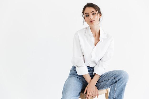 Bella giovane donna sensuale con lunghi capelli castani ricci che indossa una camicia bianca seduta su una sedia isolata sul muro bianco, in posa