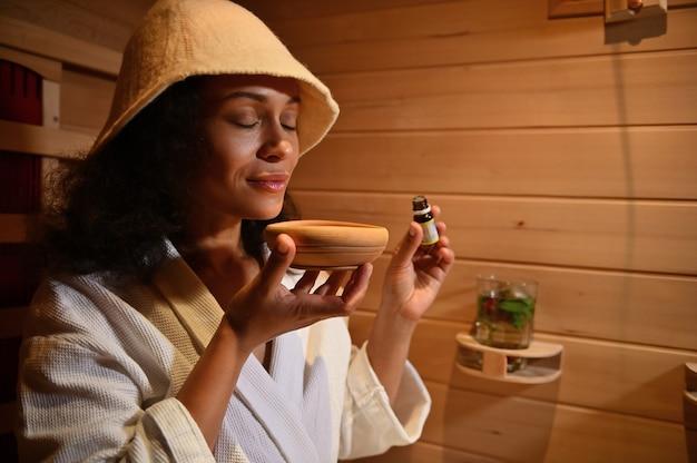 La bella donna latino-americana serena gode dell'aroma dell'olio essenziale in un mortaio di legno mentre cuoce a vapore in una sauna di legno. ritratto in primo piano
