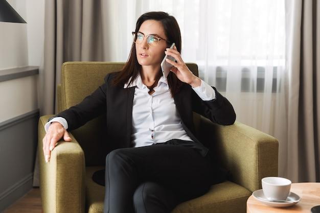 Bella seria giovane donna d'affari in abiti da cerimonia al chiuso a casa parlando al telefono cellulare.