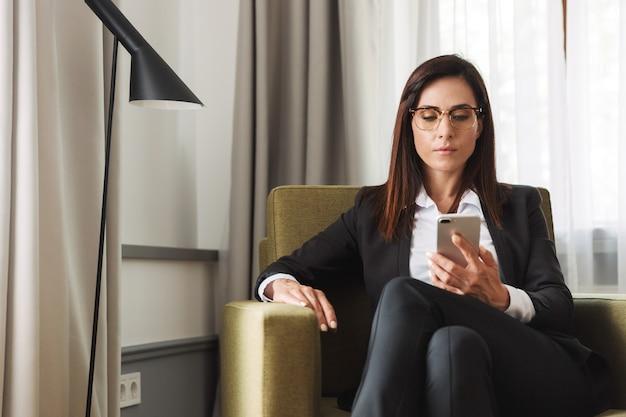 Bella seria giovane donna d'affari in abiti da cerimonia al chiuso a casa utilizzando il telefono cellulare.