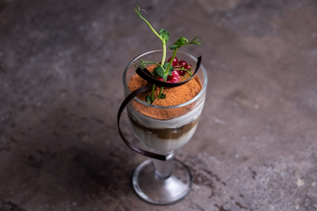 Bella porzione del piatto dessert tiramisù in un bicchiere con frutti di bosco.