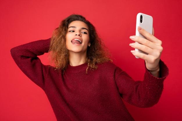 Bella giovane donna sessuale con capelli ricci che indossa un maglione rosso scuro isolato su red