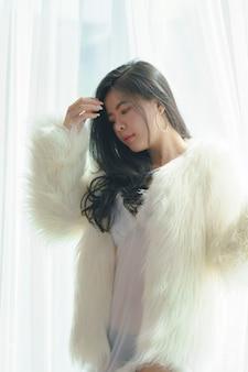 Bella donna asiatica sexy in vestito bianco felicemente