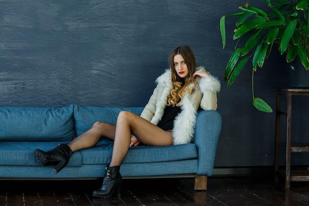 Una bella bionda sexy con un cappotto di pelle di pecora leggera si siede sul divano e posa all'interno.