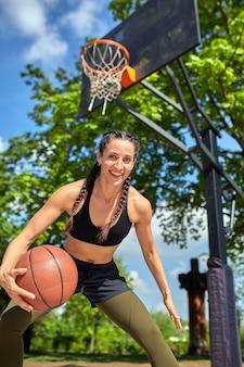 Bella ragazza sexy di forma fisica nell'usura nera di sport con l'ente perfetto con la palla del canestro al campo da pallacanestro. sport, fitness, concetto di lifestyle