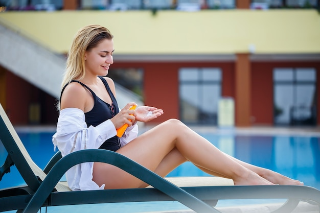 Bella ragazza sexy in costume da bagno nero si siede a bordo piscina e si applica la crema solare sul corpo