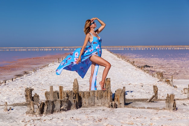Bella ragazza sexy in un vestito blu che posa su un lago salato rosa