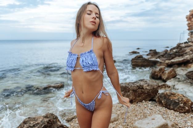 Bella ragazza sexy in costume da bagno blu sulla spiaggia.