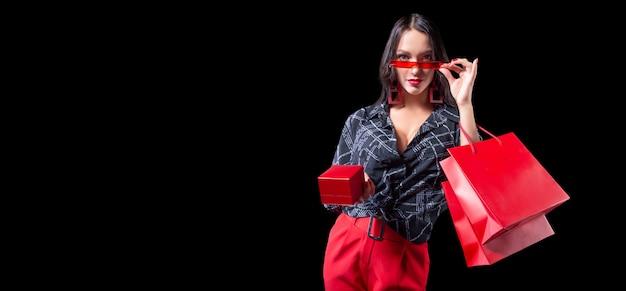 Bella ragazza sexy in occhiali in posa con pacchetti rossi e una scatola per gioielli
