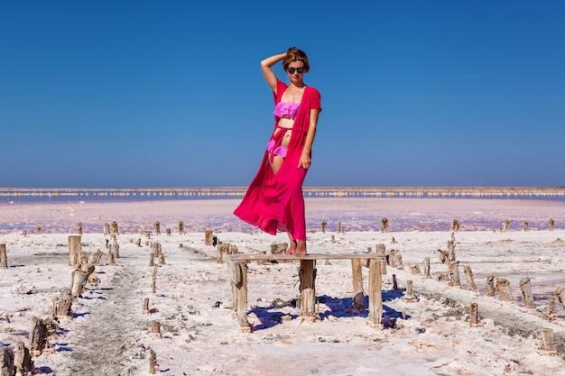 Una bella ragazza sexy in costume da bagno rosa in posa su un lago salato rosa p