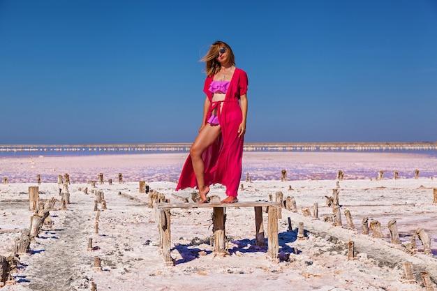Una bella ragazza sexy in costume da bagno rosa in posa su un lago salato rosa. servizio fotografico di una ragazza abbronzata su un lago rosa salato.